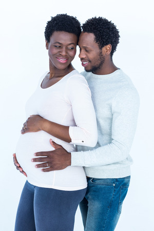 standing against: Husband touching pregnant wife belly while standing against white background Stock Photo