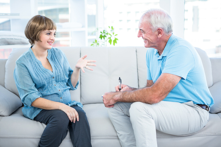 gynaecologist: Happy pregnant woman talking to gynaecologist while sitting on sofa at home