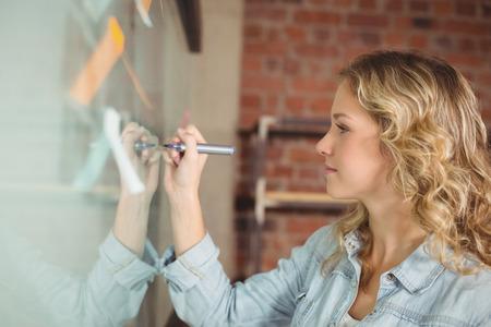 persona escribiendo: Creativo escritura hermosa empresaria a bordo de vidrio en la oficina
