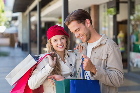 looking inside: A happy couple looking inside a bag at the mall