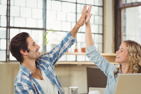 coworker: Smiling colleagues doing high five while working at office