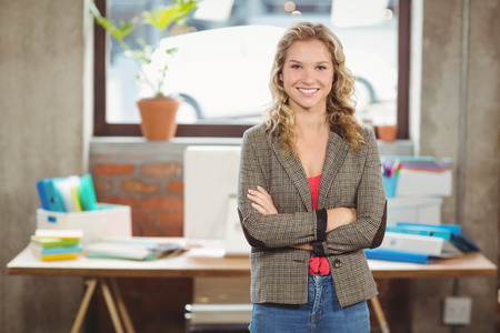 career fair: Portrait of confident smiling woman with arms crossed standing in creative office