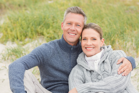 short wave: Smiling couple sitting on the sand at the beach