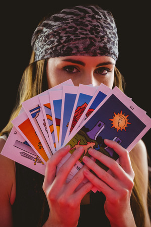 telepathy cards: Fortune teller using tarot cards on black background