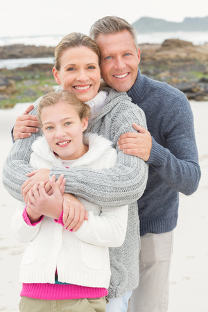 one child: Mother and father with their daughter at the beach