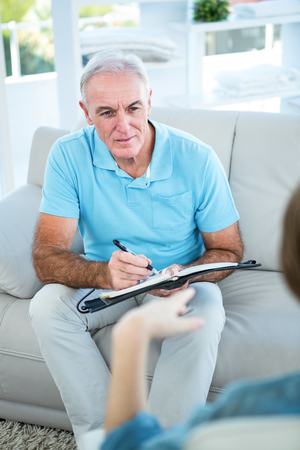 person writing: Gynaecologist talking to pregnant woman while sitting on sofa at home Stock Photo