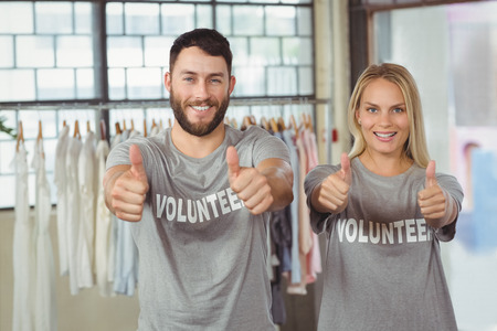 selfless: Smiling volunteers giving thumbs up in office Stock Photo