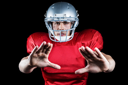 defending: Portrait of American football player defending against black background Stock Photo