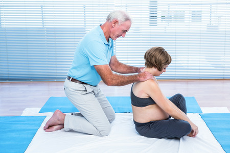 Therapist massaging pregnant woman at clinic