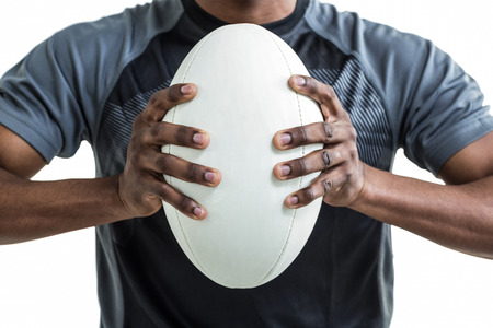 rugby ball: Cropped image of sportsman pressing rugby ball while standing over white background