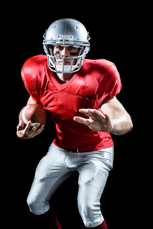 Portrait of defensive sportsman holding American football against black background Stock Photo