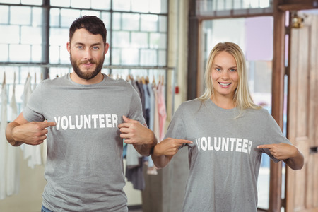 volunteer point: Man and woman showing volunteer text on tshirts in office