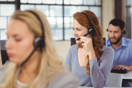 center agent: Man and women working in bright office