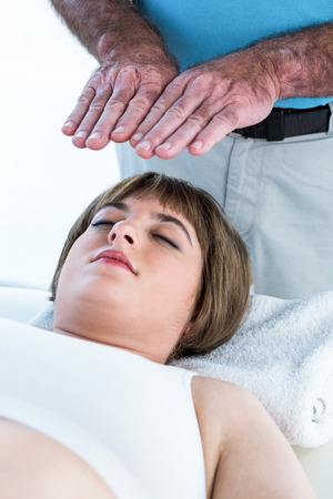 reiki: Close-up of calm woman receiving reiki treatment from male therapist at health center
