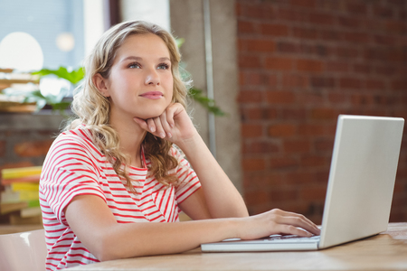 girl sit: Thoughtful woman using laptop in creative office Stock Photo