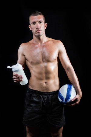 player: Portrait of shirtless man holding bottle and ball standing against black background