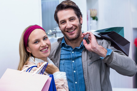clothing store: Portrait of smiling couple with shopping bags in clothing store