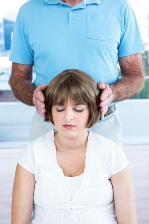 reiki: Therapist performing reiki over woman at health center Stock Photo