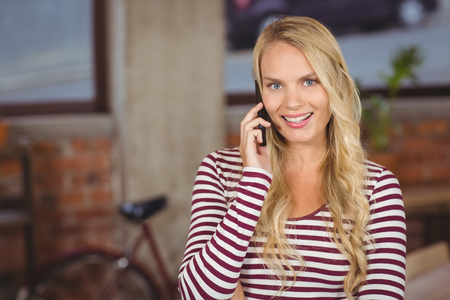 phone professional: Portrait of happy businesswoman talking over phone in office
