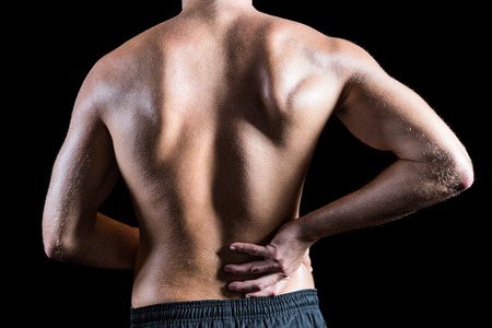 dolor muscular: Vista trasera del hombre sin camisa con dolor de espalda contra el fondo negro Foto de archivo