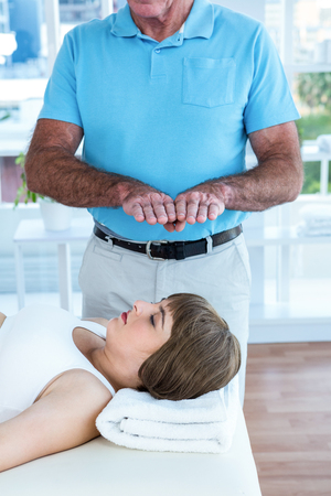 reiki: Pregnant woman relaxing while therapist performing reiki at health club