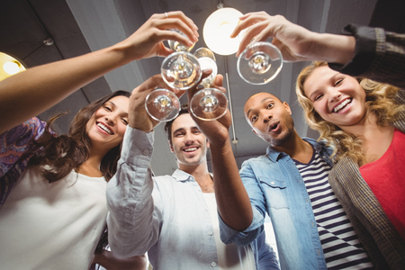 excited business woman: Low angle portrait of happy colleagues toasting with champagne in creative office Stock Photo