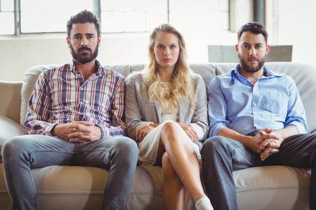legs crossed at knee: Portrait of serious business people sitting on sofa in office