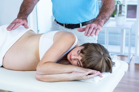 closed club: Male therapist performing reiki over pregnant woman at health club Stock Photo