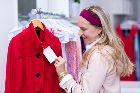 clothing store: Smiling woman looking at price tag in clothing store