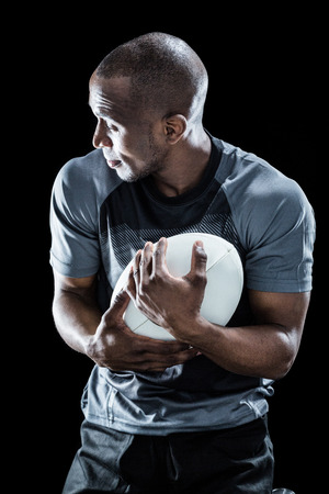 catching: Rugby player looking away while catching ball against black background