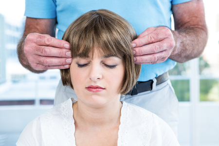 reiki: Woman with eyes closed receiving reiki from male therapist at health club Stock Photo