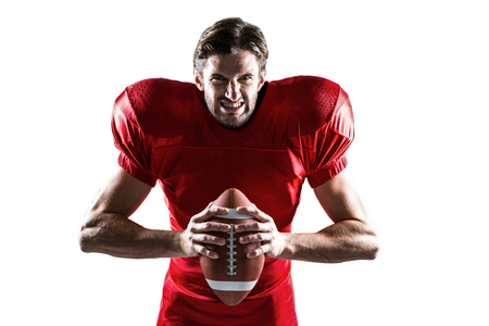 cut the competition: Portrait of aggressive American football player in red jersey holding ball on white background Stock Photo
