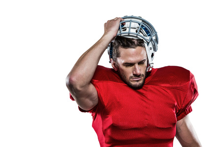 removing: American football player in red jersey removing helmet against white background