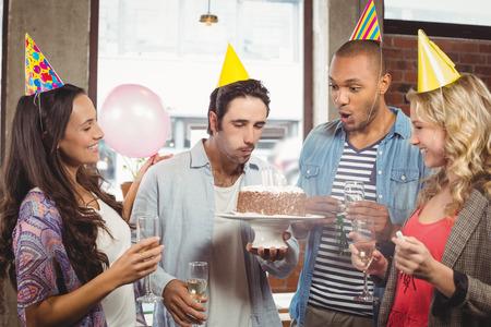 velitas de cumpleaños: Hombre que sopla las velas en la torta, mientras que sus colegas sonriente en la Oficina