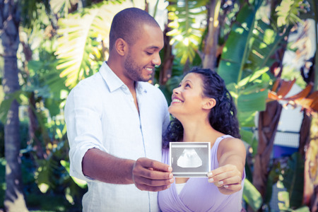 sonograma: Happy man with pregnant wife holding sonogram against white background