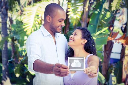 sonogram: Hombre feliz con la esposa embarazada sosteniendo sonograma contra el fondo blanco