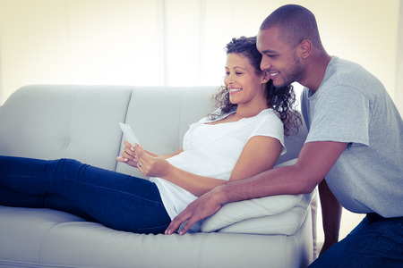 Young couple with sonogram on sofa at home