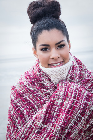 warm clothing: Beautiful woman wrapped up in warm clothing at the beach