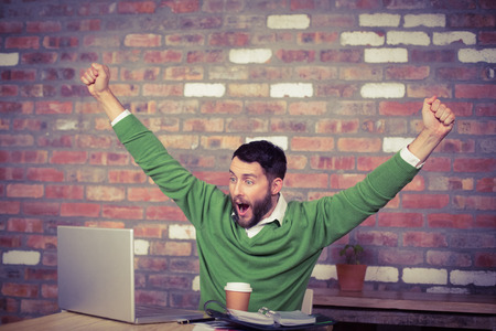 cool man: Happy businessman cheering while looking at laptop in office
