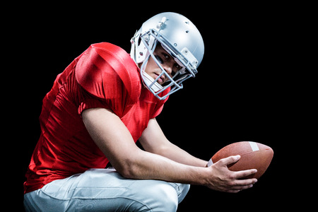 crouching: Portrait of American football player crouching while holding ball against black background