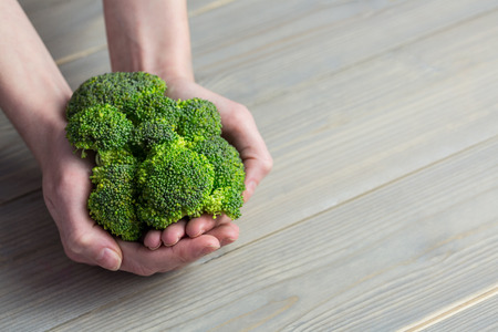 woman hands up: Woman showing fresh green brocolli in close up Stock Photo