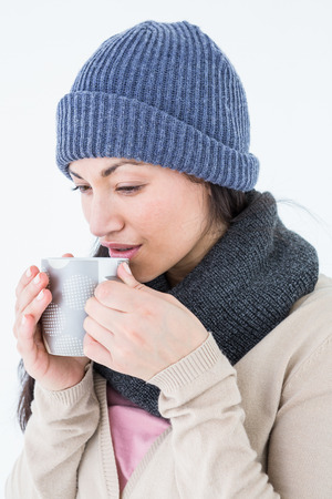 hot beverage: Smiling brunette drinking hot beverage on white background