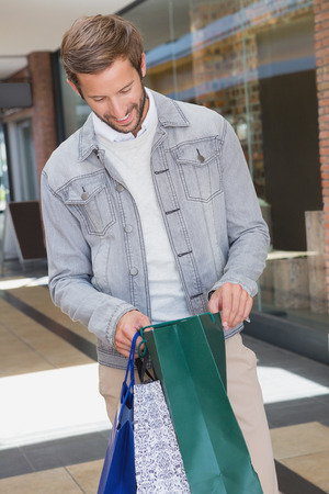 looking inside: Young happy smiling man holding shopping bags and looking inside in front of a store Stock Photo