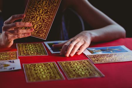 teller: Fortune teller using tarot cards on black background
