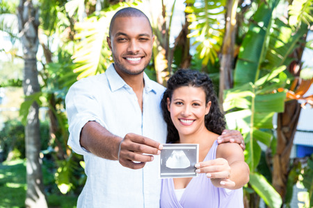 sonograma: Retrato de feliz esposo con la esposa embarazada sosteniendo sonograma contra el fondo blanco