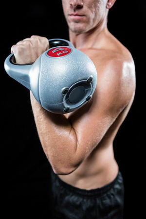 free weight: Midsection of shirtless sportsman working out with kettlebell against black background Stock Photo