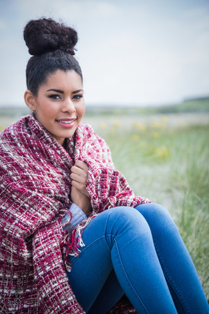wrapped up: Beautiful woman wrapped up in warm clothing at the beach