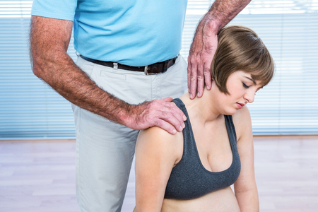 closed club: Therapist massaging shoulder of pregnant woman at health club