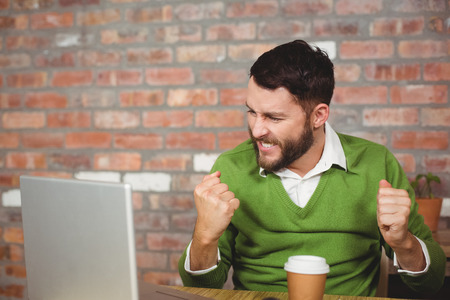 clenching: Excited businessman clenching fist while looking at laptop in creative office Stock Photo