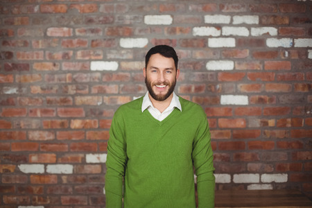 cool: Portrait of happy businessman standing against brick wall